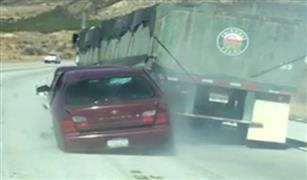 شاهد بالفيديو ..  ماذا حدث لسيارة امريكي علقت  بشاحنة علي الطريق السريع بكاليفورنيا