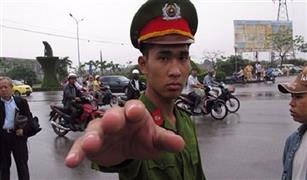 شرطي فيتنامي يتشبث بغطاء محرك سيارة سيارة أجرة لمنع سائقها من الهرب