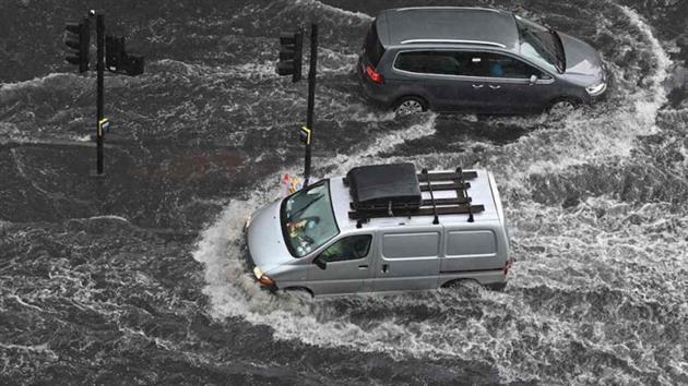 شاهد رجل يستخدم سلما للوصول إلى سيارته الغارقة في مياه الفيضان